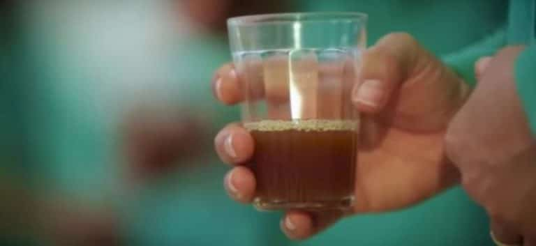 pessoa segurando copo com cha de ayahuasca